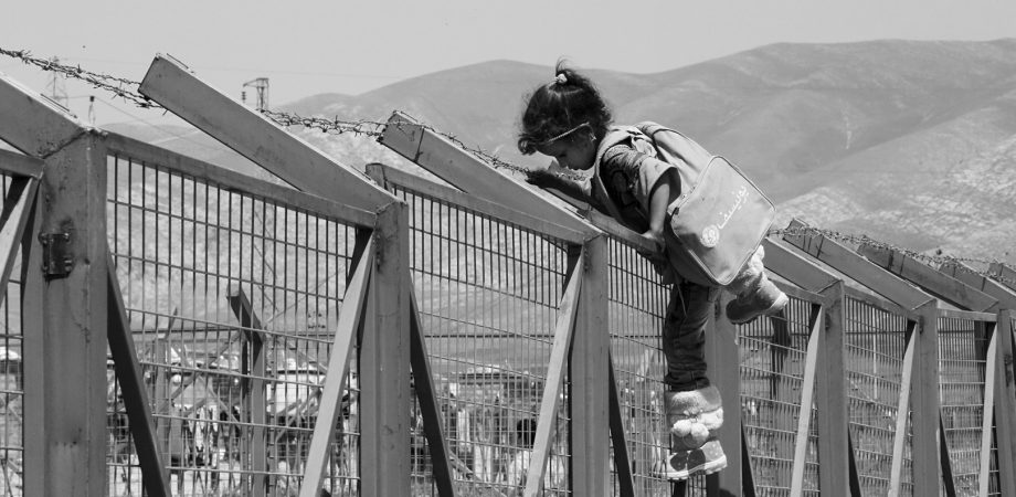 Photo of young girl climing over fence